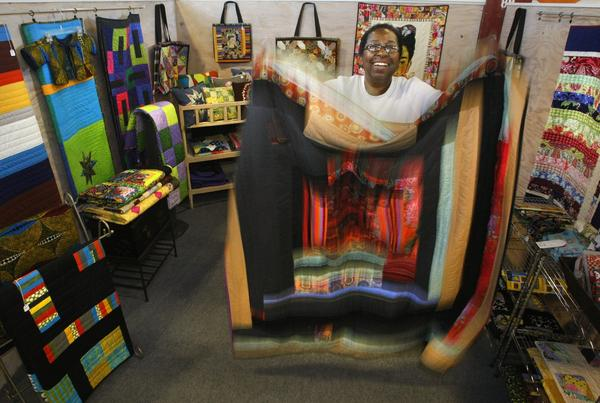 Patsy Johnson, 58, holds one of the many quilts that she designs, makes and sells at Crafted at the Port of Los Angeles. Johnson quit a 25-year career as an insurance broker, saying she was tired of corporate life.