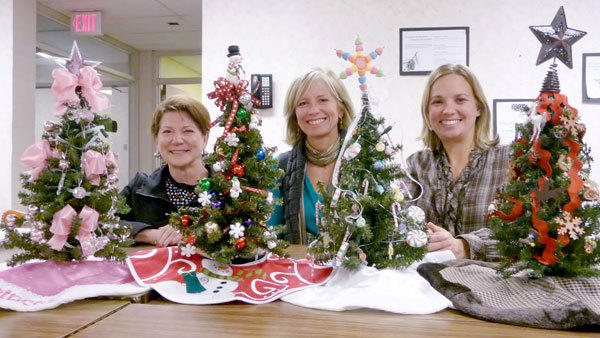 Pam Karbowsky, Janice Lampert and Dana Bensinger (l-r) show a selection of small decorated trees that will be used as centerpieces at the 2012 Extreevaganza. These trees, along with many others of varying sizes and decoration, will be among the silent and live auction items that will be sold at the Dec. 7 gala fundraiser to benefit the Otsego County Community Foundation at Treetops Convention Center.