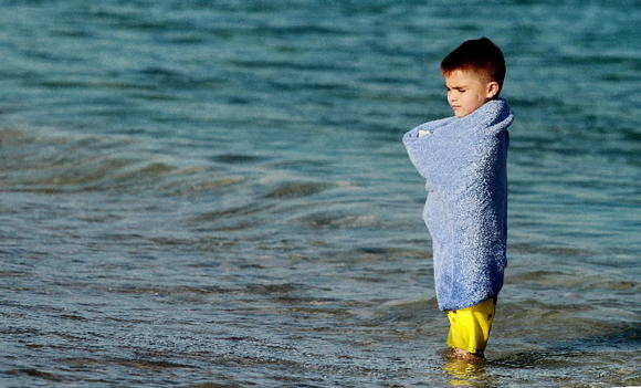 Israel Maese, 4, of New Mexico, stays warm in a towel during a recent visit to Delray Beach. Expect warm afternoon temperatures today.
