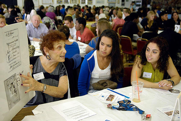 Boca Raton High School student Suzanne Dean and Wellington High School student Gigi Marcano (right) listen to Holocaust survivor Anita Hoffer, 79, of Boca Raton, who is showing copies from her German passport and telling how she survived the Holocaust during a presentation Tuesday to about 250 high school students.