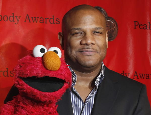"Voice actor Kevin Clash arrives with the puppet Elmo for the 2010 Peabody Award ceremony at the Waldorf Astoria in New York. Clash is the puppeteer who controlled the iconic ""Sesame Street"" character Elmo."