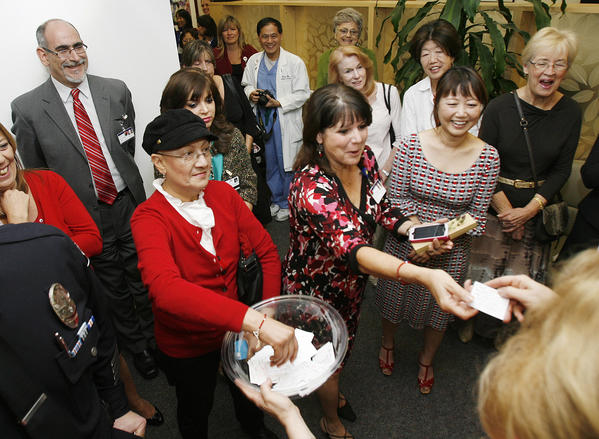 Cancer survivor Guadalupe Mendoza, of Los Angeles, in red, draws the winning name in an iPod raffle at Glendale Adventist Medical Center in Glendale for the resumed annual visit by the Rose Court to visit staff and patients on Tuesday, November 13, 2012.