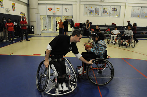 U.S. Paralympian Steve Serio helps Leslie Rodriguez, 12, maneuver her wheelchair before she and other students got a chance to play wheelchair basketball at the Boys & Girls Club of Hartford  Tuesday afternoon.  He, and fellow paralympian Katie Holloway, shared  their inspirational stories with local students. The event was sponsored by The Hartford. Serio, of Long Island, was a bronze medal recipient in the 2012 Paralympic Games. He has been playing wheelchair basketball since he was 14 years-old.