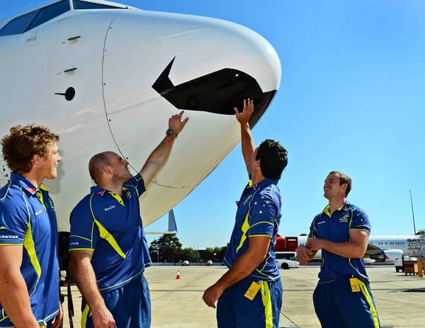 Australian rugby players Michael Hooper, left, Stephen Moore, Dave Dennis and Pat McCabe admire a Qantas jetliner with a mustache painted in its nose to mark Movember, the worldwide fundraiser to help fight prostate cancer.