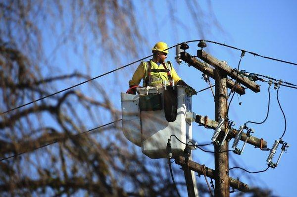 A worker positions himself to repair electrical lines as Long Islanders continue their cleanup efforts in the aftermath of Superstorm Sandy.