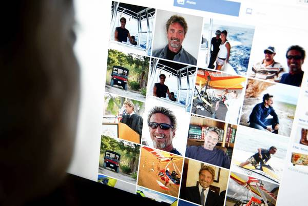 Belize police have urged John McAfee to come forward, saying he is only a person of interest, rather than a murder suspect. McAfee reportedly fears he'll be killed if police find him. Above, a woman views a Facebook page belonging to McAfee.