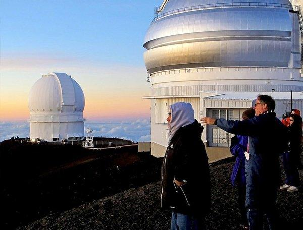 People watch a sunset in front of the Gemini Northern Telescope at the summit of Hawaii's Mauna Kea. Beyond is the Canada-France-Hawaii Telescope.