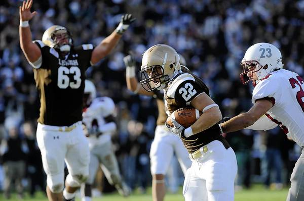 Lehigh's Matt Fitz (22) center, sprints into the end zone in front of Lafayette's Evan McGovern (23) right, in the second quarter at Goodman Stadium Saturday, November 19, 2011.
