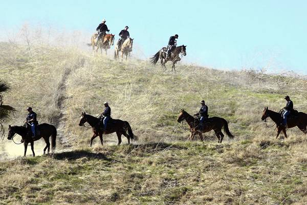 Members of the Los Angeles Police Department's mounted platoon descend after searching a hillside behind the El Sereno Recreation Center in the El Sereno area of Los Angeles.