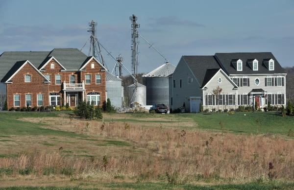 "Grain silos at the Mullinix ""home farm"" on Howard Road in Dayton are visible behind the adjacent high-end homes built along Triadelphia Road, part of a new residential subdivision."