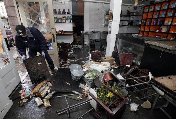 A man cleans up his store in New York's South Street Seaport after Superstorm Sandy.