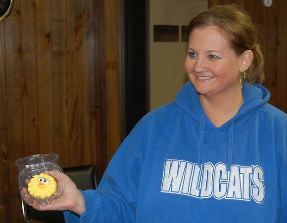 Christy Baldwin shows Junction City officials on Tuesday one of the Sesame Street-themed cupcakes being sold to support the city's toy drive.
