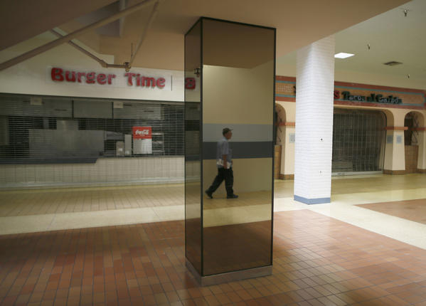 A man walks past empty stores in the deserted Carousel shopping mall in San Bernardino, California. he city of about 210,000, some 65 miles east of Los Angeles, filed for bankruptcy on August 1, joining the Bay Area city of Stockton as a test case for whether financially troubled municipalities can shed bond payments and possibly pension obligations via bankruptcy court.