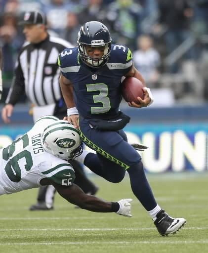 Seattle quarterback Russell Wilson, who grew up in Richmond, rushes against outside linebacker DeMario Davis of the New York Jets during the Seahawks' 28-7 home victory.