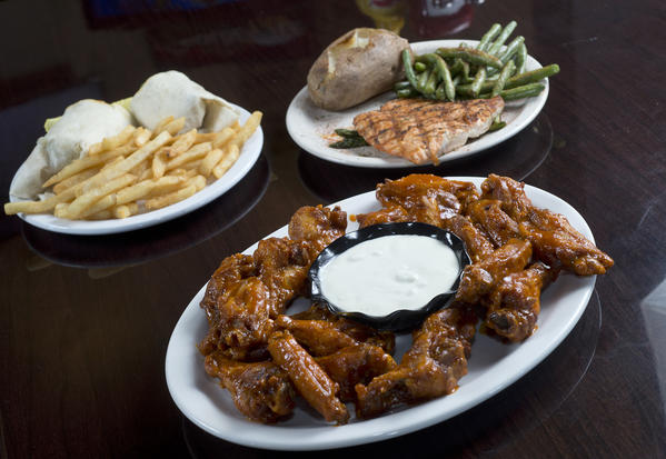Platters of chicken wings, spiced rubbed grilled salmon and cheesesteak wrap are pictured inside the 1760 Pub N Grille in Trexlertown on Wednesday, November 14, 2012.