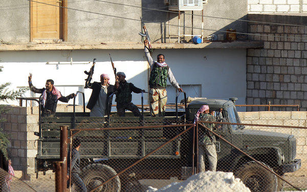 Syrian opposition fighters celebrate on the strategic Syrian border town of Ras Ayn.