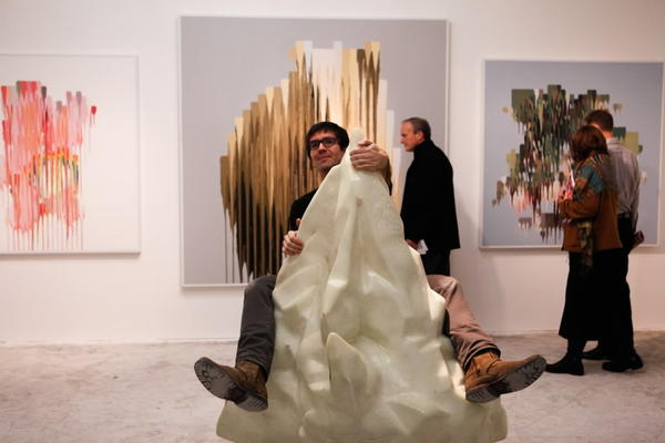 "Artist Jake Myers riding Sarah and Joseph Belknap's ""How I learned to stop worrying,"" a fiberglass model of a glacier, in Octagon Gallery's booth."