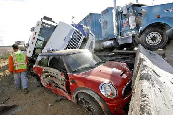 A construction worker walks past a crash on the northbound I-5 freeway before Western Ave. involving two big rigs and a Mini Cooper on Wednesday, November 14, 2012.