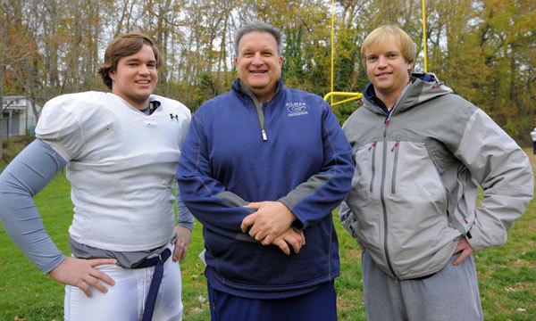 Gilman coach Biff Poggi, center, is pictured with two of his three sons, Henry, left, and Sam, right, after a recent practice for the No. 1 Greyhounds, who will meet No. 2 Calvert Hall in the MIAA A Conference championship Saturday night at Towson University.