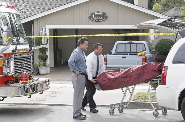 The body of a woman who died in a house fire is wheeled out at 2201 Heather Lane in Newport Beach on Wednesday.