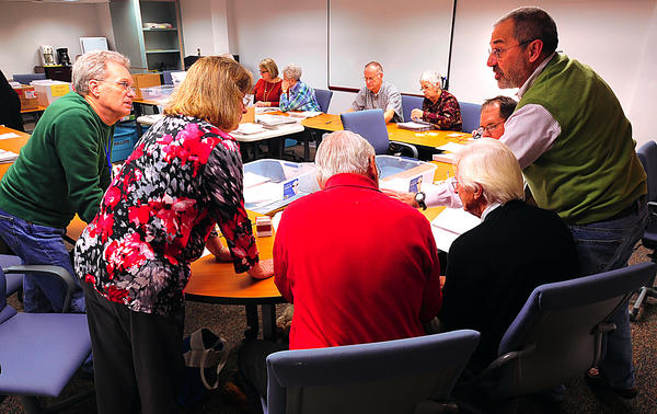 Washington County Election Board members, from left: Bruce Field, Tammy Downin, Carroll Earp, and board president John Benchoff confer with board attorney Roger Schlossberg Wednesday during the board's counting of provisional ballots from the election held last week.