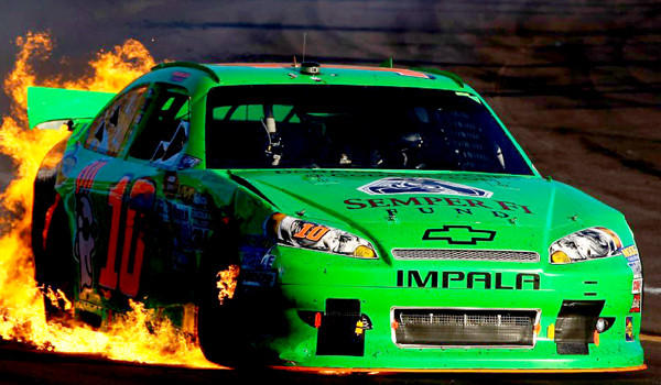 Danica Patrick drives the wrecked No. 10 GoDaddy.com Chevrolet as flames shoot from the back of her car after an incident in the NASCAR Sprint Cup Series AdvoCare 500 at Phoenix International Raceway on Nov. 11, 2012.