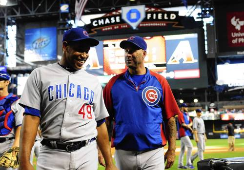 Cubs manager Dale Sveum and pitcher Carlos Marmol walk off the field, celebrating a 7-2 win against the Diamondbacks.