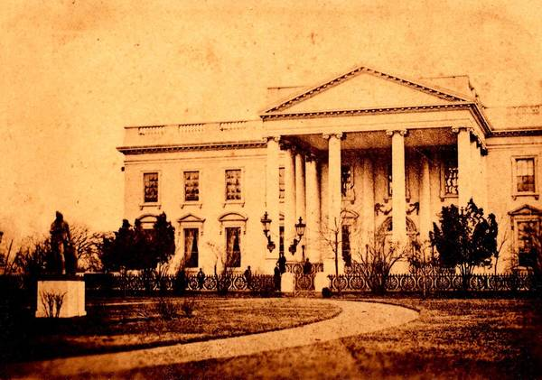 This March 6, 1865 photo, provided by the Collection Keya Morgan/LincolnImages.com, and carrying the seal of photographer Henry F. Warren, shows the White House with several figures standing in front of it. Photography collector Morgan says the photo is the only known photograph of Lincoln standing in front of the White House, and the first photo ever to have been taken of a President in front of the White House.