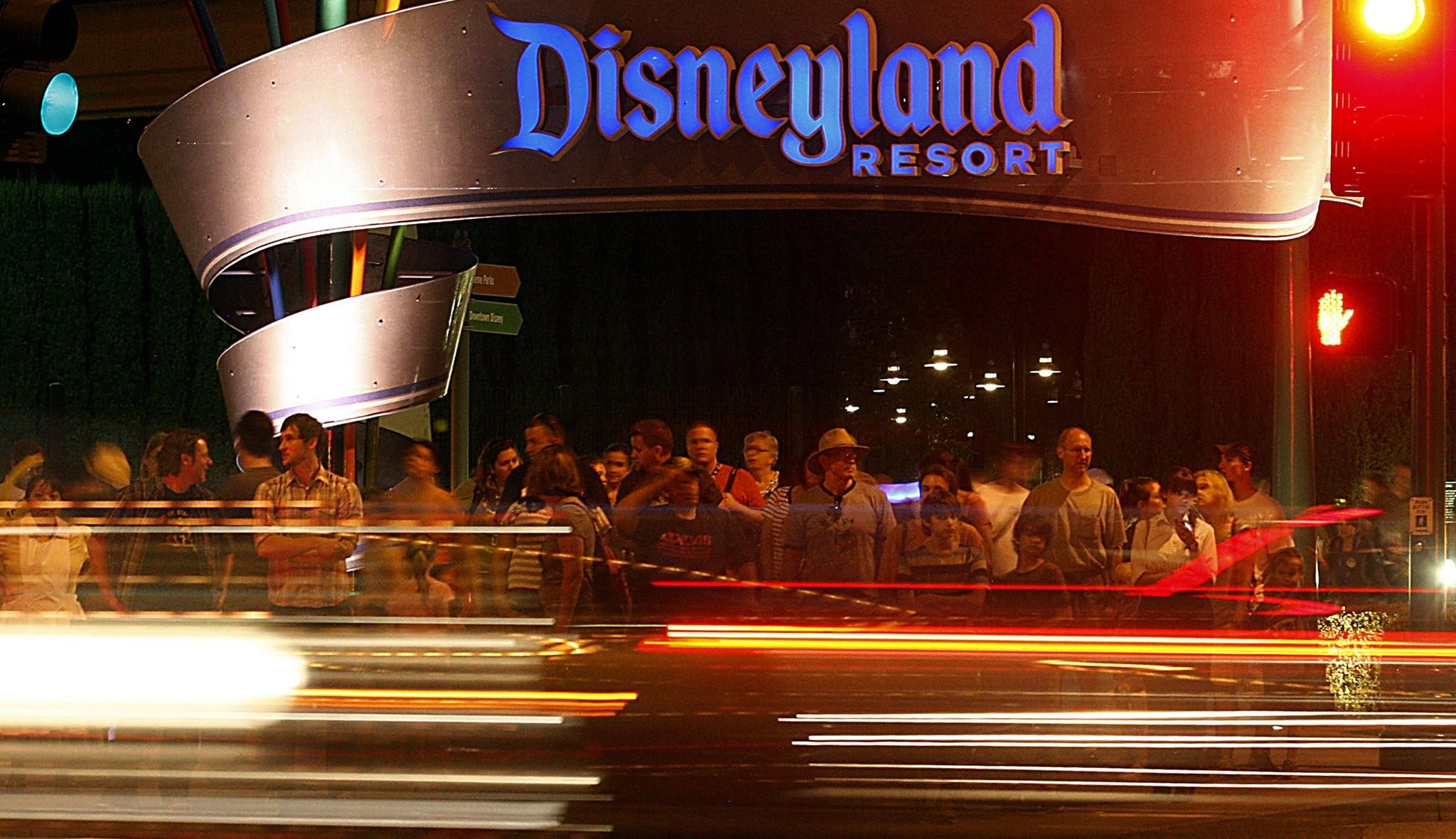 Disneyland visitors wait to cross Harbor Boulevard on its eastern side. The theme park has lived up to Walt Disney's aim to create a fantasyland hidden away from the metropolis around it, though its architecture has seeped out onto the boulevard to beckon tourists and residents alike. (Luis Sinco / Los Angeles Times)