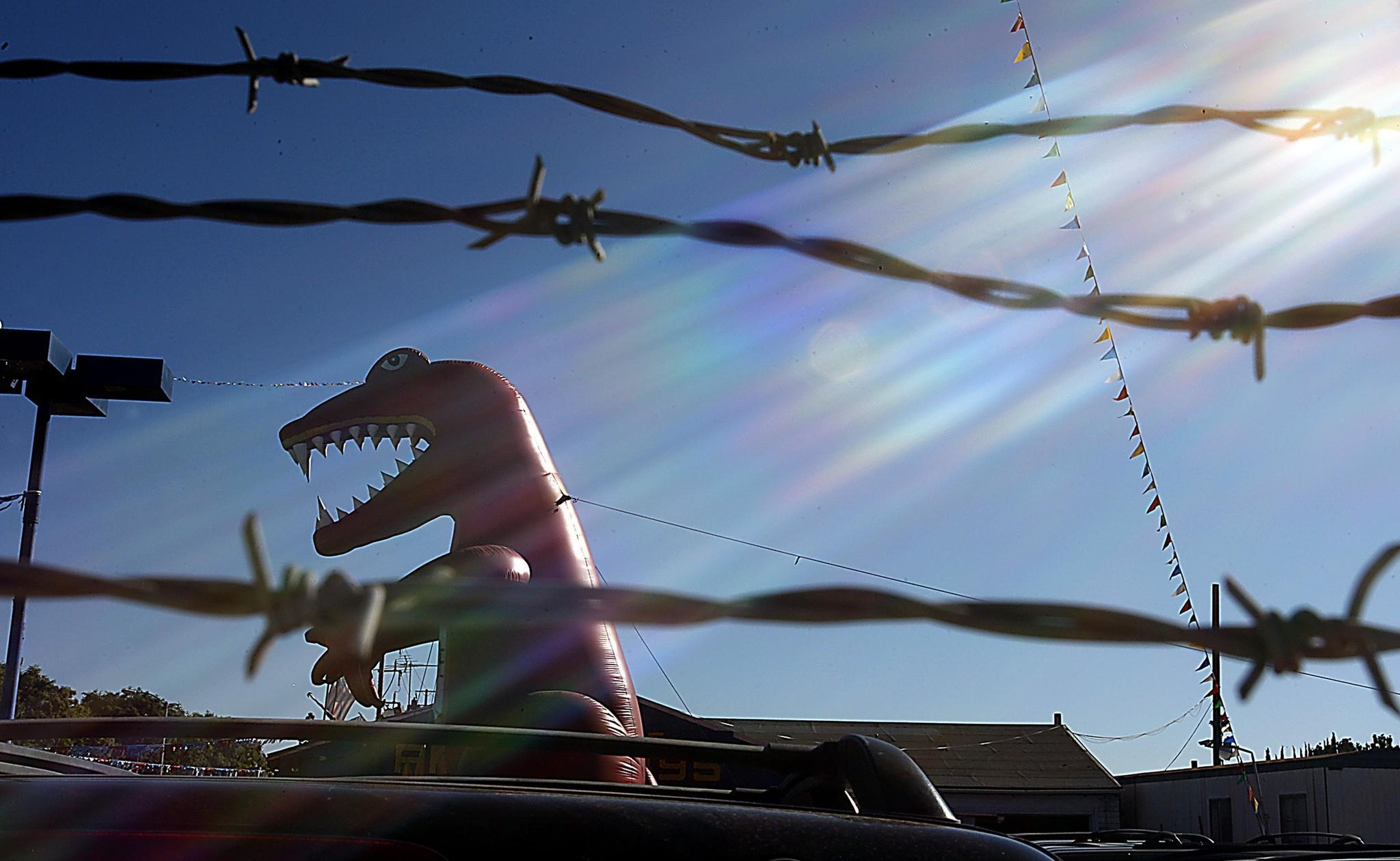 An inflatable dinosaur towers over one of the many used car lots along Harbor Boulevard in Santa Ana.