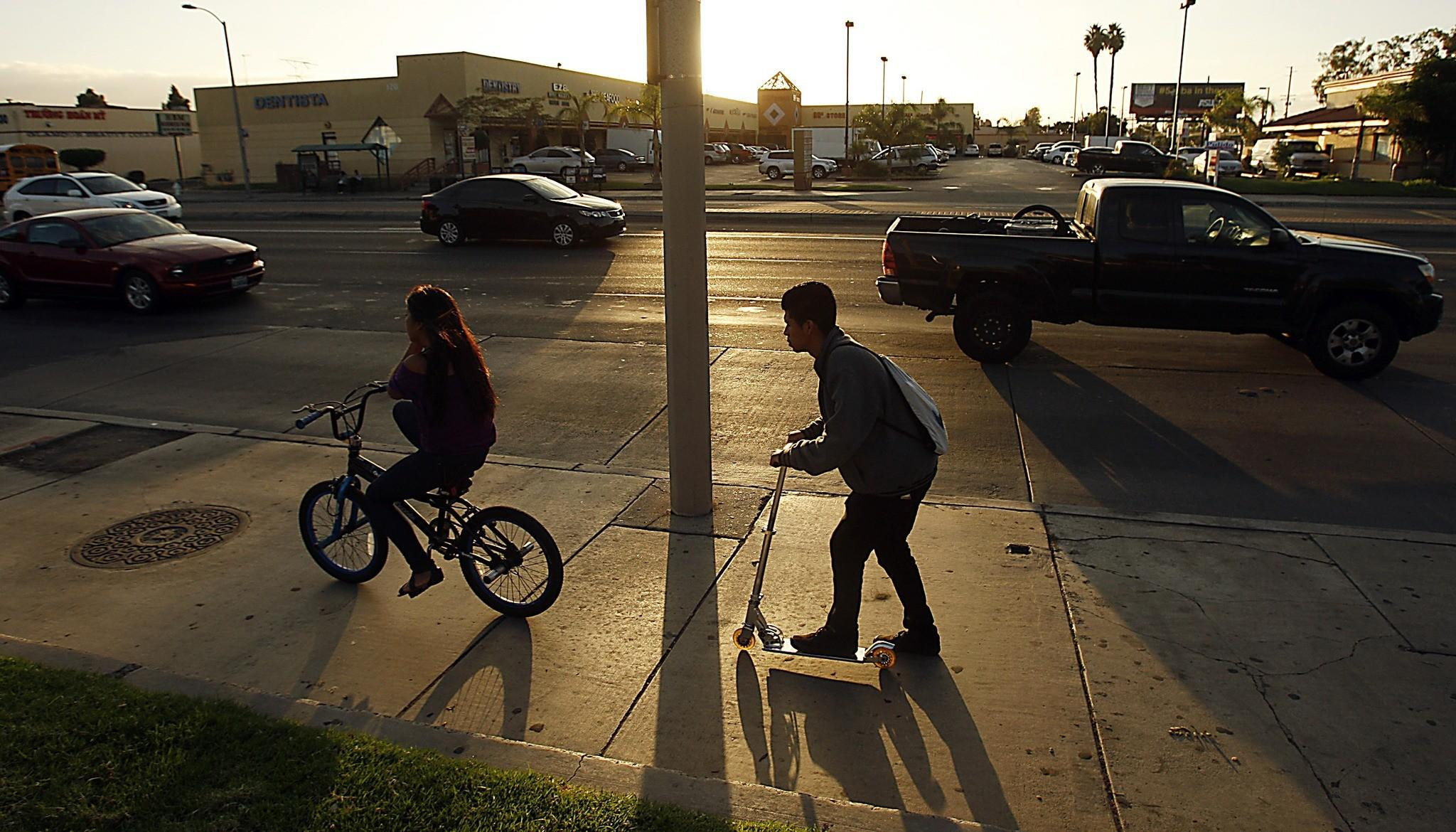 Kids scoot down Harbor Boulevard in Santa Ana as late afternoon traffic rolls along a landscape of strip malls. Despite real estate development, the boulevard has seen little change over the years. There is no equivalent of the light-rail expansion that is remaking L.A., neither is there a large infusion of bike lanes or a rethinking of pedestrian access that would better engage with the landscape. (Luis Sinco / Los Angeles Times)