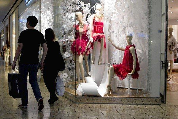 Shoppers carry bags while passing in front of a store at the Fair Oaks Mall in Fairfax, Va.