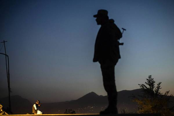 An Afghan police officer keeps an eye out while a man prays on a hilltop in Kabul.