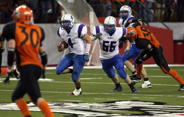 Warner's Clay Rozell, center, finds room to run as Canistota's Boone DeKramer (30) moves in during last week's Class 9A football championship game. Behind Rozell is teammate Brian Peterson (55). The 9A game pitted a pair of unbeaten foes against each other.