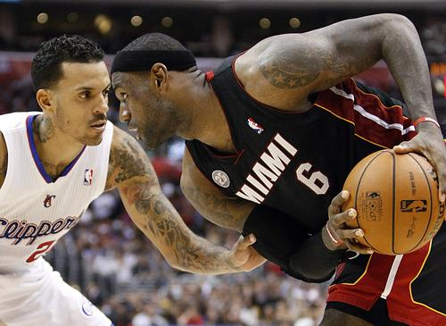 Clippers forward Matt Barnes plays tight defense on Heat forward LeBron James during their game Wednesday night at Staples Center.