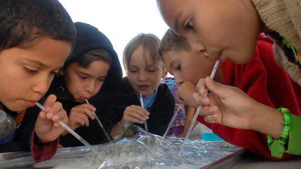 "Students use plastic straws to blow bubbles in a tray Wednesday during Science Discovery Day at Ben Hulse Elementary School in Imperial. ""It is a way of showing geometrical figures and surface tension,"" volunteer teacher Adriana Ramirez said of the bubble project."