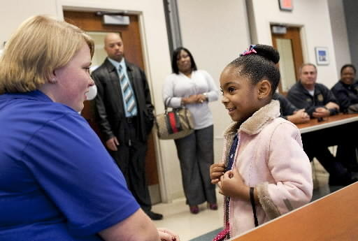 Jailah Driver, 4, talks to dispatcher Sarah Sledge as Jailah's parents, Jamorn and LaQuan, look on at Newport News Police Headquarters on Wednesday.