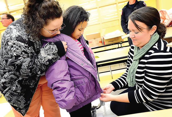 Pangborn Elementary School School-Family Liaison Anna Haupt, right, helps second-grader Mikeyia Longfellow, 8, try on her new winter jacket Wednesday during the Firefighters Coats for Kids program at the school. At left is Mikeyia's older sister, Makayla McDermott, 13. The program is an effort by firefighters in the United States and Canada to help families stretch limited financial resources, according to a news release from Hagerstown Professional Firefighters IAFF Local 1605.