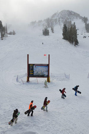 Snowboarders advance on the line for chair lift 1 at Mammoth Mountain.