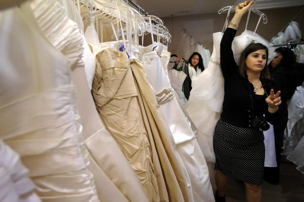 WEST HARTFORD-11/14/12- Jolene Madison, a sales consultant at Camille Bridal, pulls dresses from the rack for prospective brides Wednesday. A dozen future military brides took part in the Brides Across America event at the shop where more than 40 dresses were given away for free to brides who either served in the military over the last five years or who have their fiancees serving in the military. Irene Zalevsky, the owner of Camilles, has been giving away bridal gowns around Veterans day for the past four years and says it is her way to give a little something back as a thank you to those who serve.