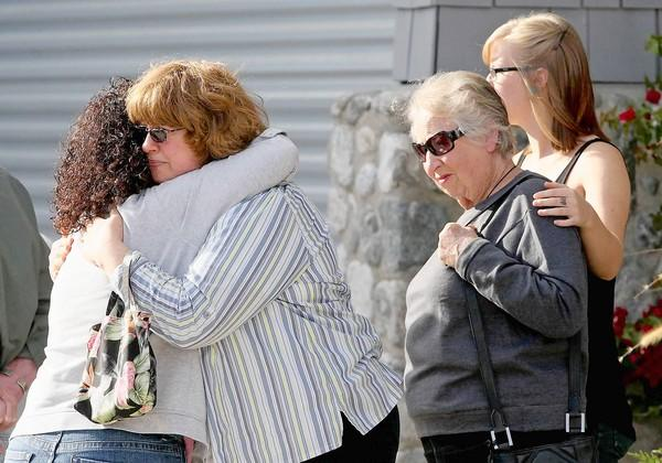 Family and friends react to the news of a loved one who died in a house fire at 2201 Heather Lane in Newport Beach on Wednesday. The woman, second from right, said she is the sister of the homeowner.