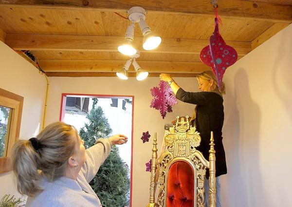 Judy Kearby, left, and Susan Leonhard hang decorative snowflakes in Santa's workshop for this weekend's opening of the Sawdust Festival's Winter Fantasy.