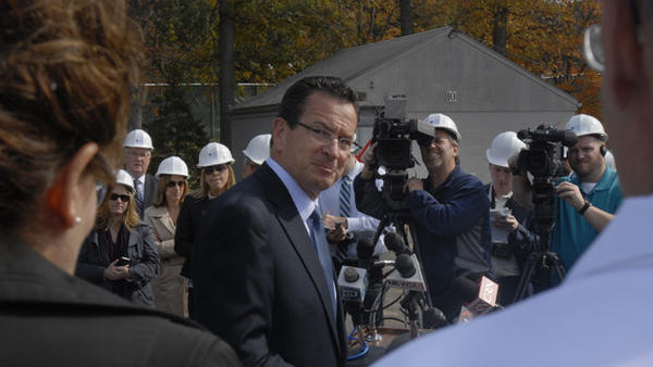 Gov. Dannel P. Malloy looks back at UConn President Susan Herbst during a ceremony Oct. 17 marking the beginning of work on Jackson Lab's new facility there.