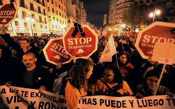 "Protesters hold placards reading ""Stop evictions"" as they attend a demonstration during a general strike in Valencia, Spain."