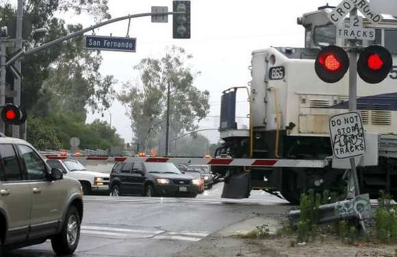 Vehicles wait to cross as an approaching train passes by on the tracks at Doran St. and San Fernando Road in Glendale on Friday, June 17, 2011.