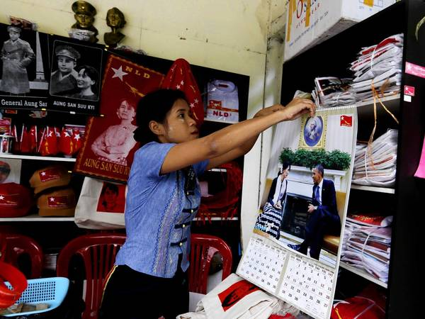A member of Myanmar's National League for Democracy party hangs a calendar with a photo of party leader Aung San Suu Kyi and President Obama in the party's gift shop in Yangon. Obama will visit the nation next week.
