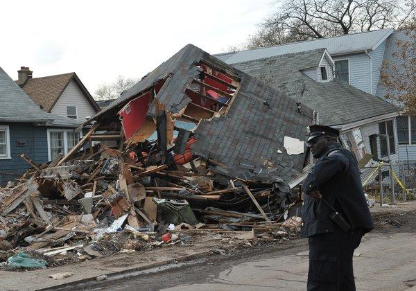 A police officer stands outside a collapsed house on Staten Island. Parts of Staten Island and Long Island remained without power in the aftermath of Sandy.