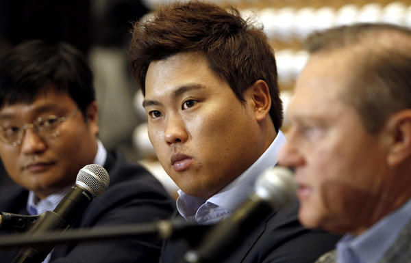 Pitcher Ryu Hyun-jin is flanked by agent Scott Boras, right, and Boras' South Korea representative Al Chung during a news conference Thursday in Newport Beach.
