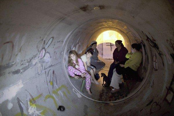 Israelis take cover in a concrete pipe used as a bomb shelter in Kiryat Malachi. Three residents of an apartment building there were killed by a rocket fired from the Gaza Strip.