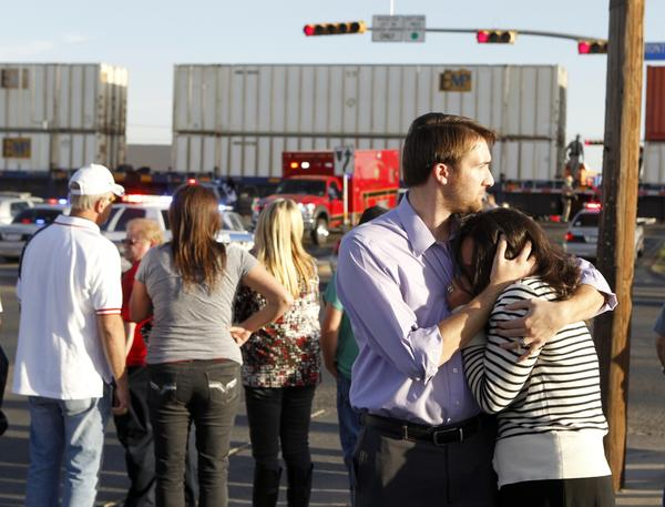 Bystanders react as emergency responders work at the scene of a fatal train-truck collision at a parade for veterans in Midland, Texas.